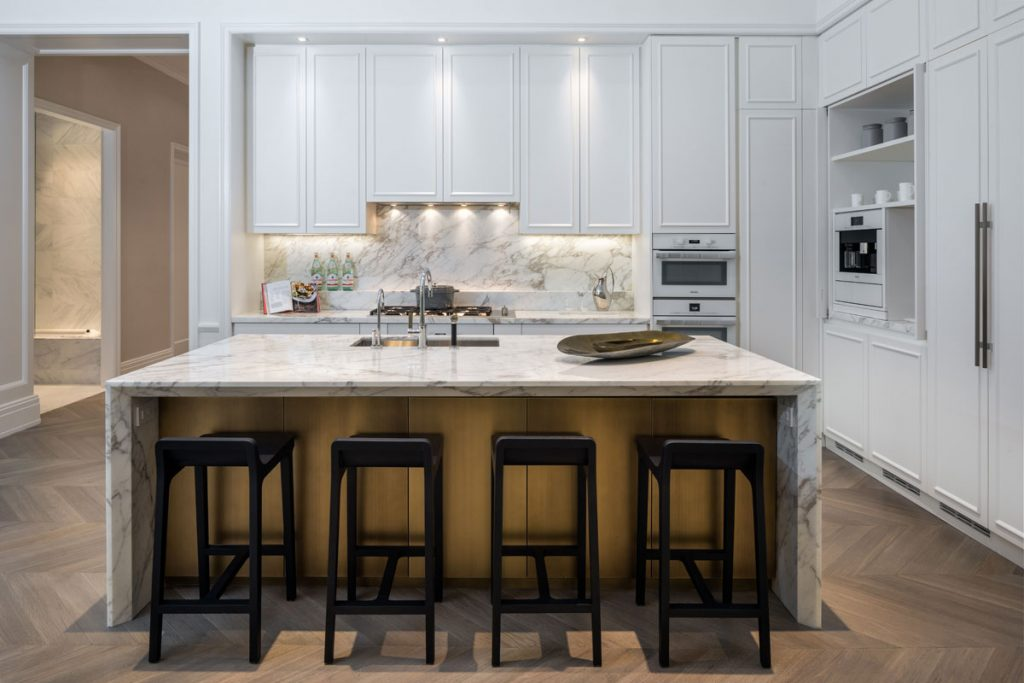 Modern white kitchen design with marble island and black bar stools