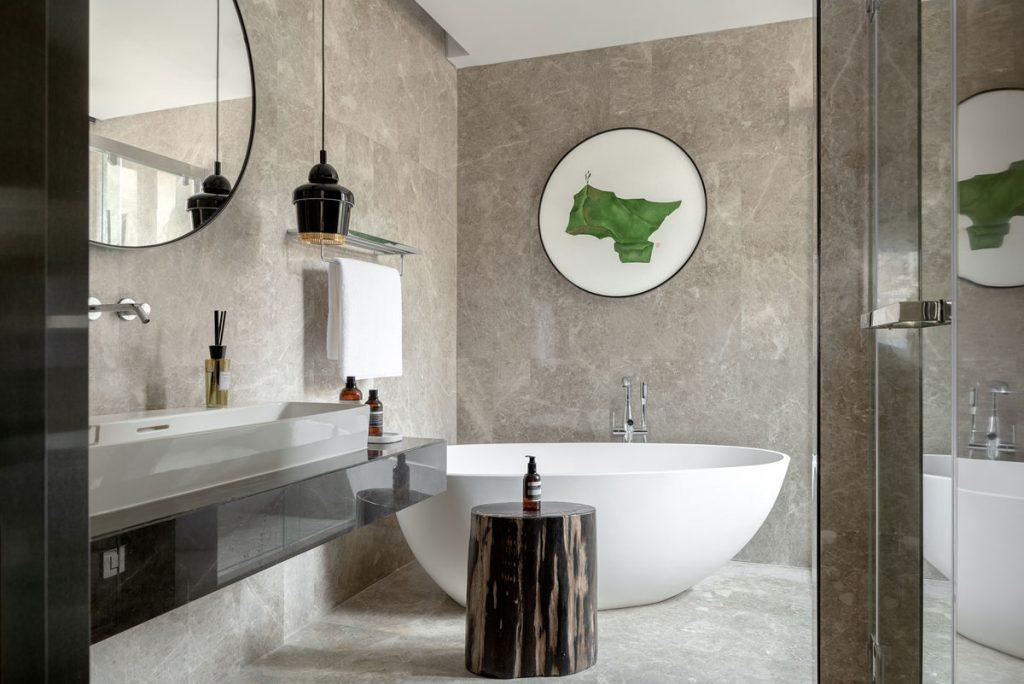 Concrete surfaces in modern bathroom design with oval bath tub