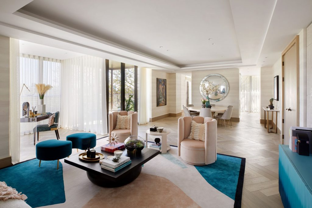 Open plan living area with light wood floor and statement rug