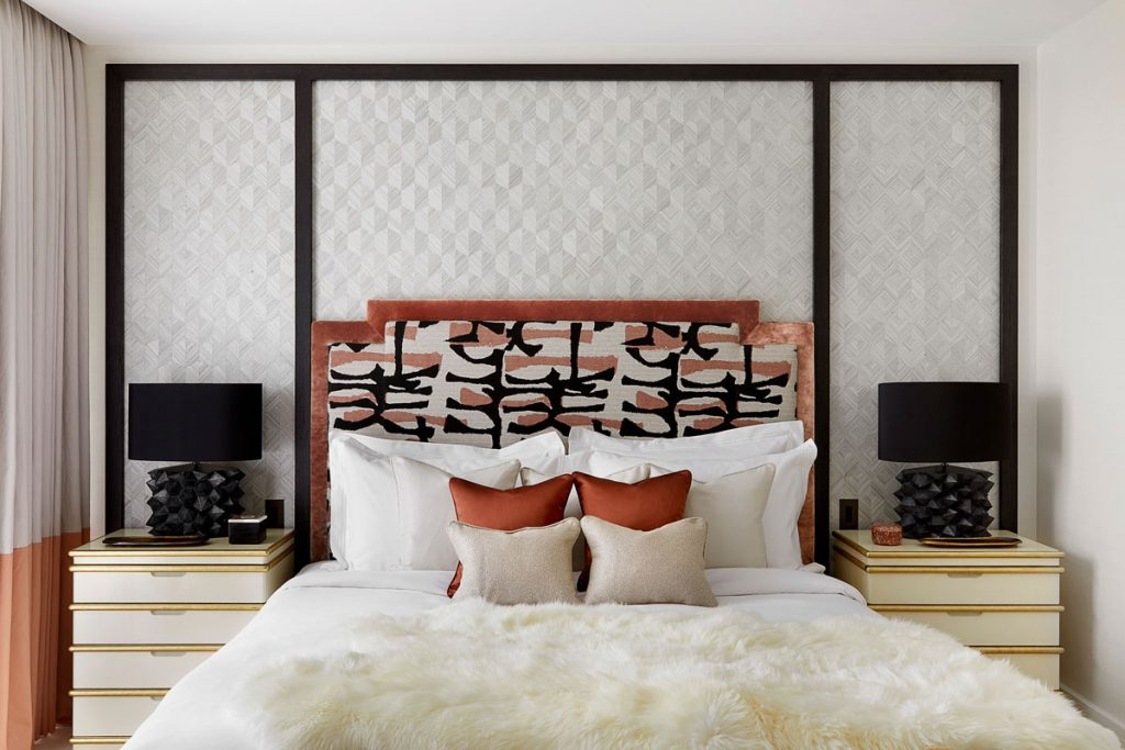 Close up of bedroom furnishings with artistic headboard and luxury bedding