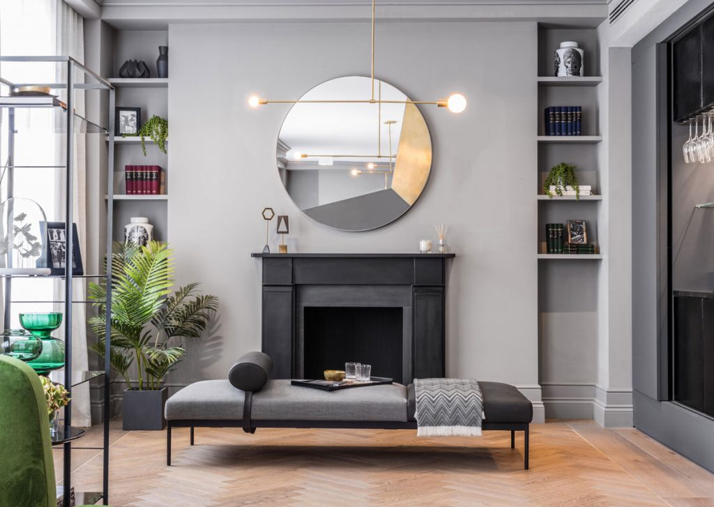 Interior decor featuring black fireplace with contemporary circle mirror