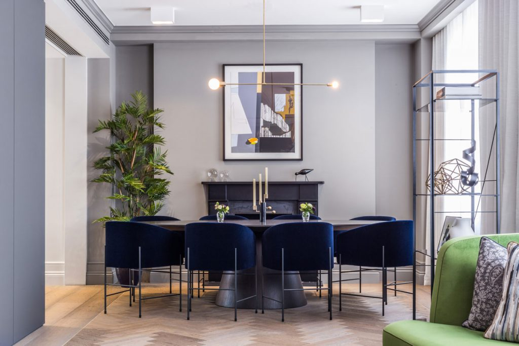 Luxury dining room interior design with blue velvet seating and abstract art