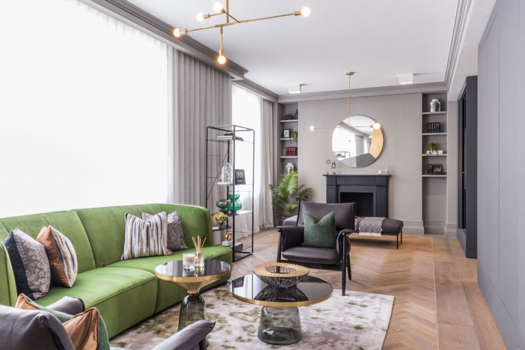 Living room interior with statement green sofa and parquet wood flooring