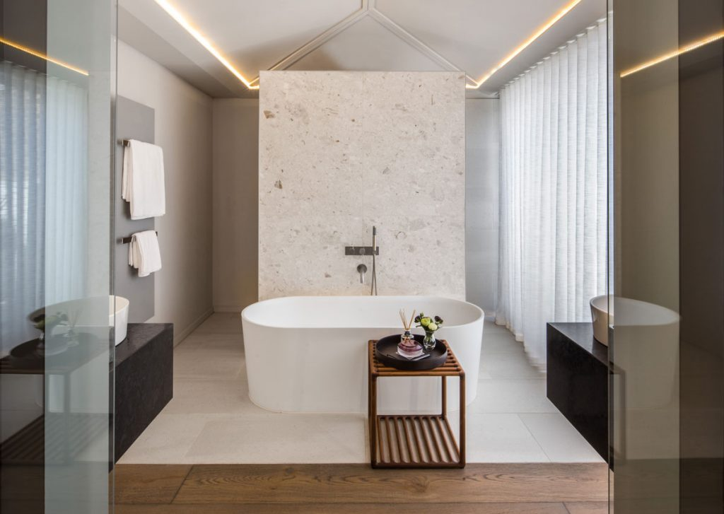 Bathroom interior design with marble detail and central free standing bath tub