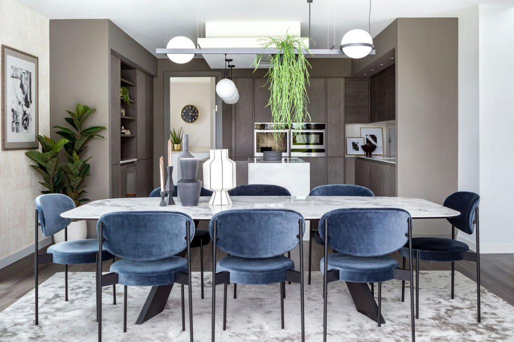 Modern dining room interior setting with velvet blue seating and grey kitchen cupboards