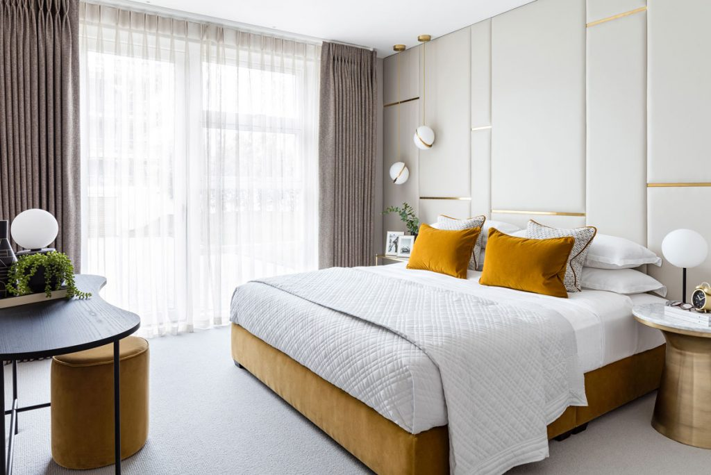 Bedroom interior styling with panel wall feature and velvet yellow details
