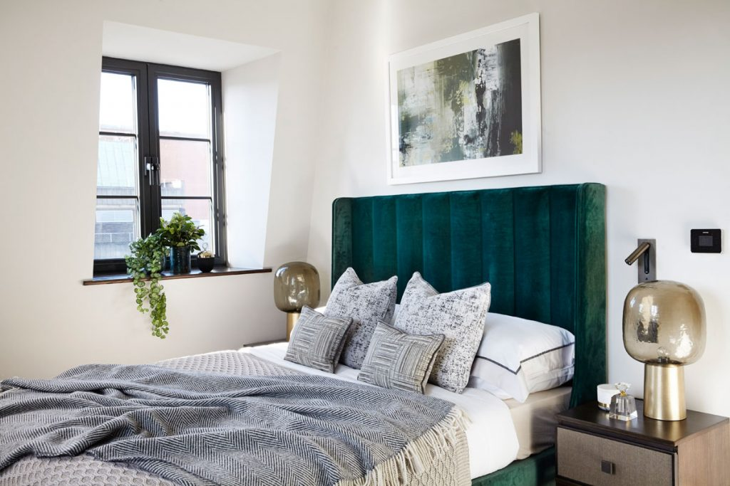 Bedroom interior with green velvet headboard and gold details